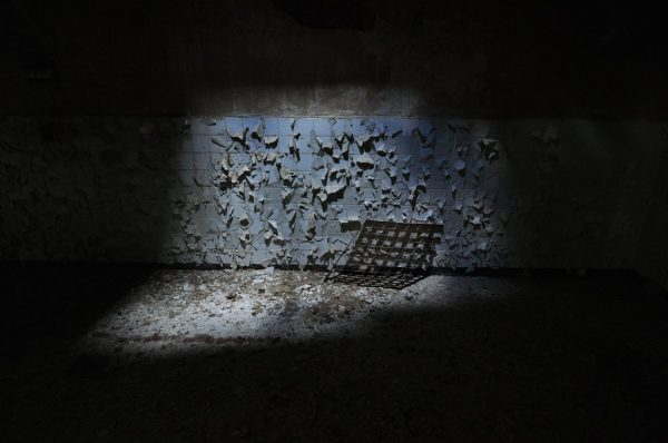 A Grate resting against a peeling wall at the Kaserne Krampnitz in Potsdam, Germany