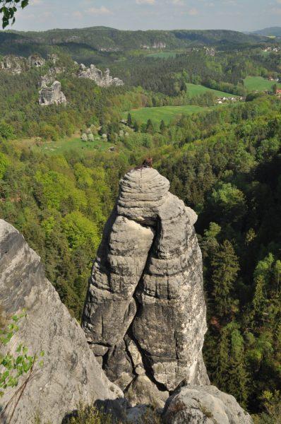 A Rock Climber perched atop a sandstone column
