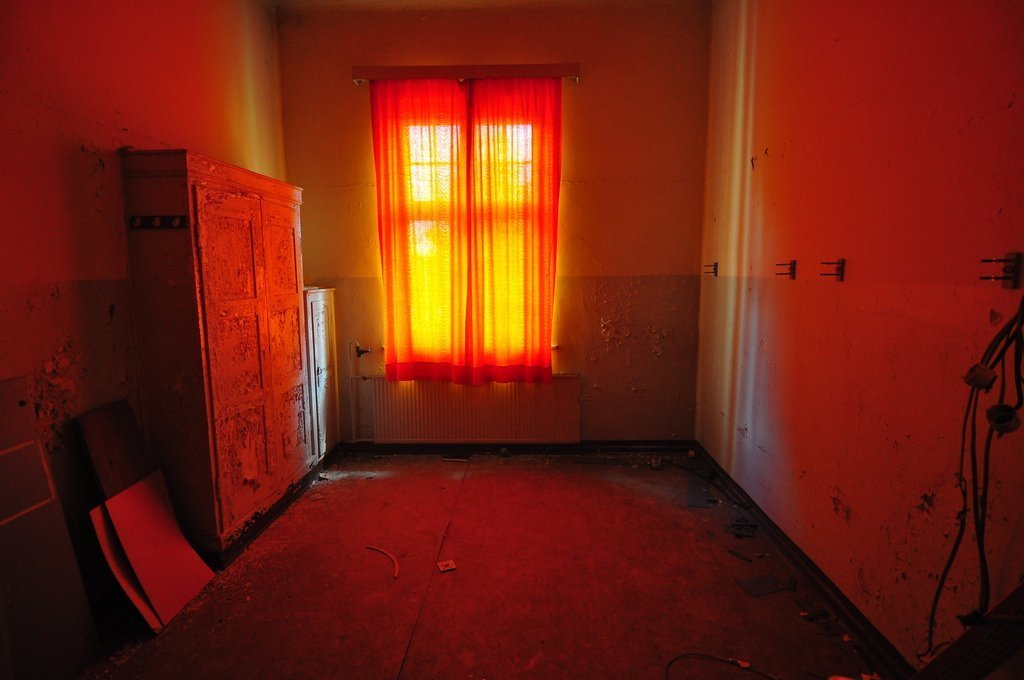 an abandoned patients room bathed in orange light