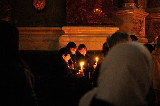 3 women holding candles during easter mass in St Stephens Basilica in Budapest, Hungary