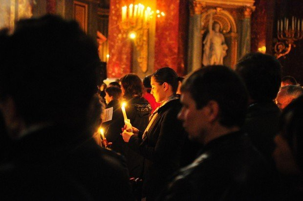 A Woman holding a Candle and Praying