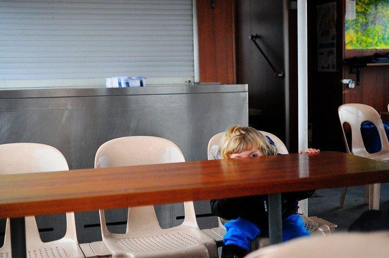 child peeking over table